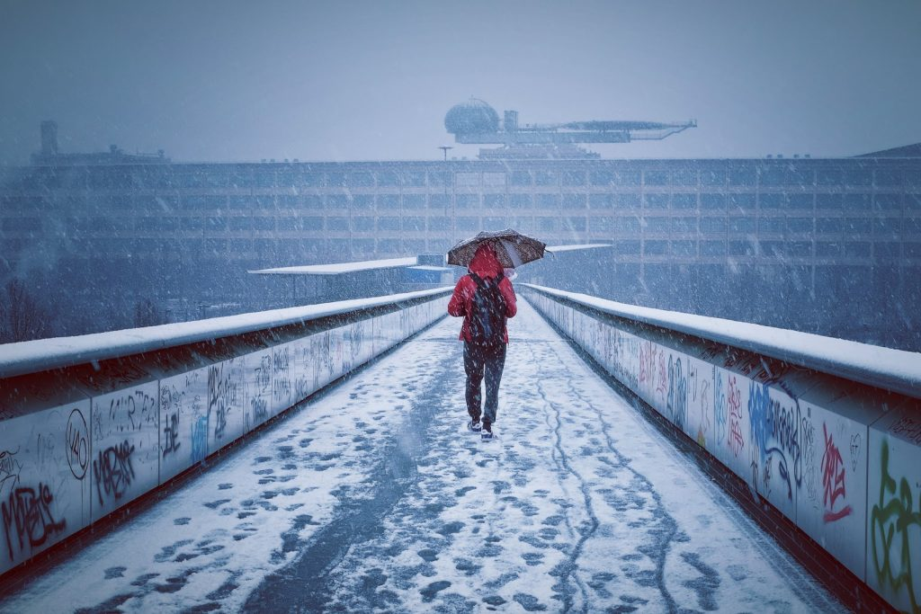 Person in a red hoodie walking down a snowy walkway, holding an umbrella against the falling snow.