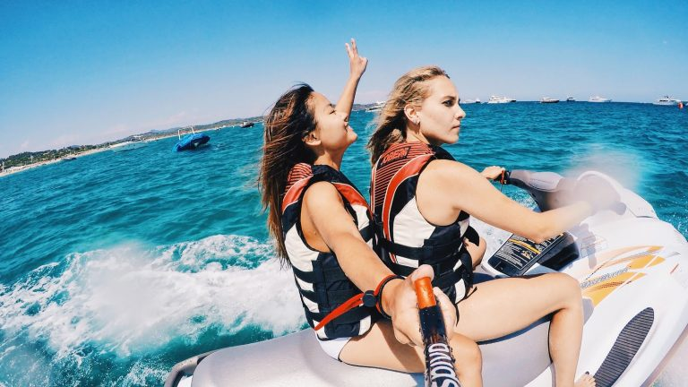 Two women on a jet-ski taking a photo of themselves using a selfie stick.