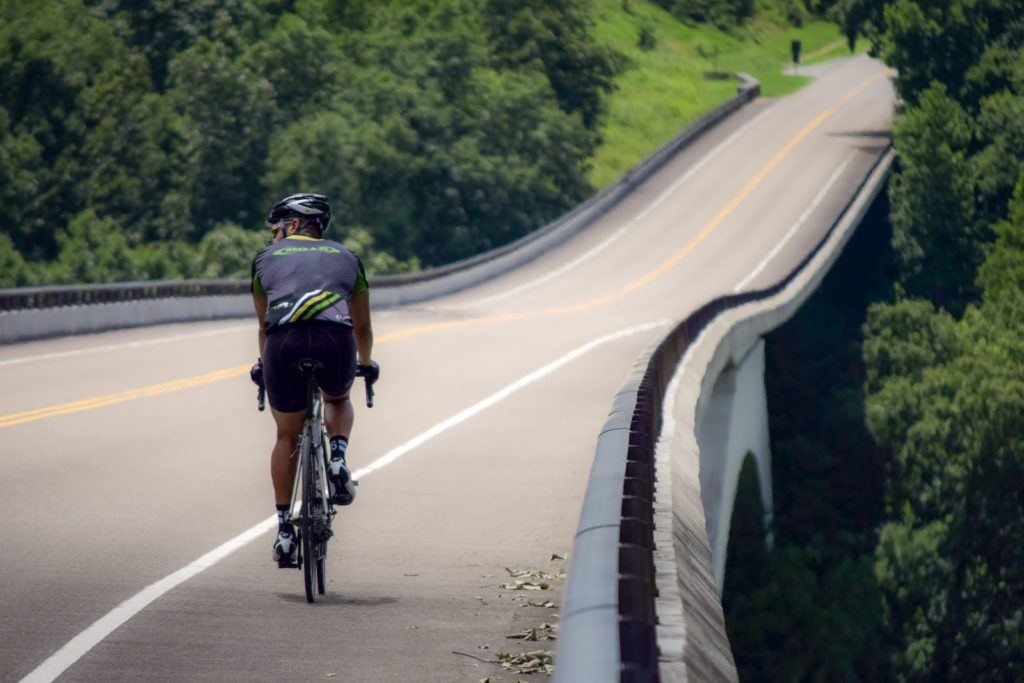 a man riding a bicycle on the shoulder of an empty road.