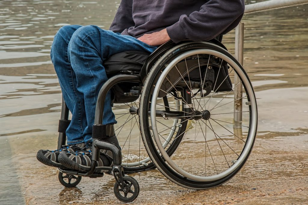 Man seated in a wheelchair shown from the waist down.