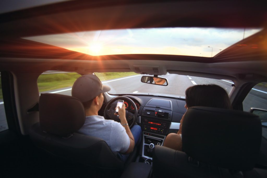 a man driving a car while driving with a woman in the passenger seat.