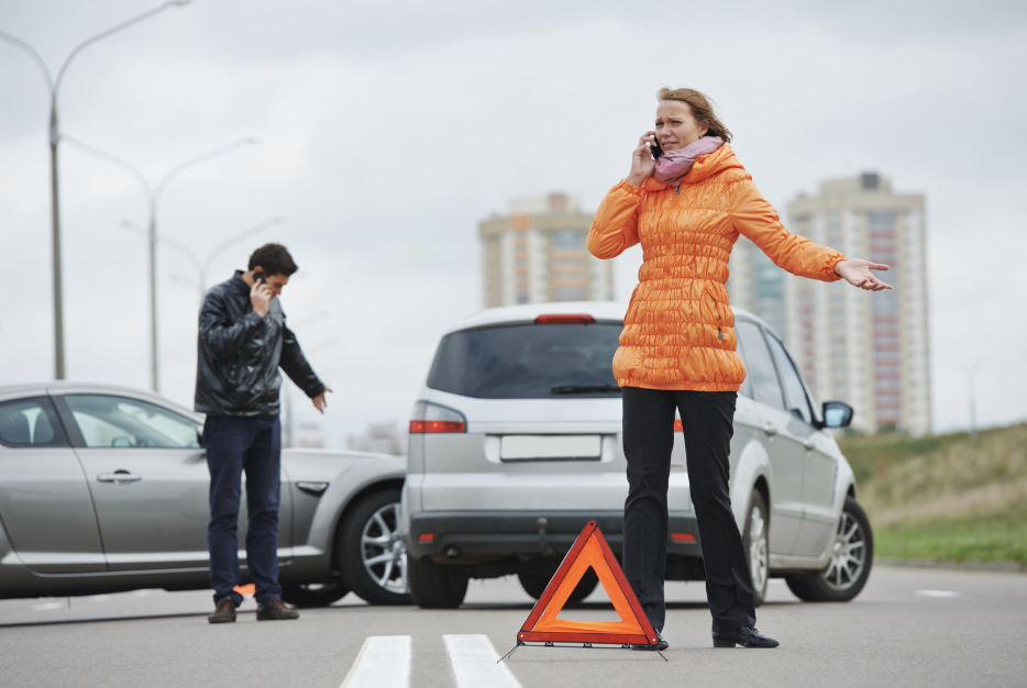 Two people talking on cellphones, standing in front of two vehicles that have hit one another.