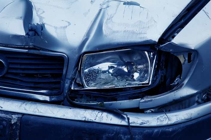close-up of the front of a car with a smashed headlight and fender.
