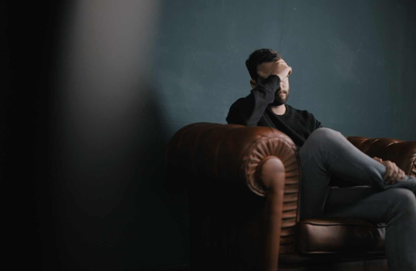 Man sitting on a couch holding his hand to his face.