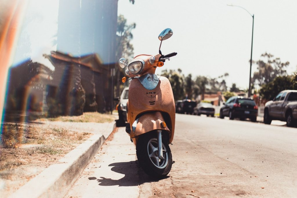 A motorized scooter parked on the side of the road.
