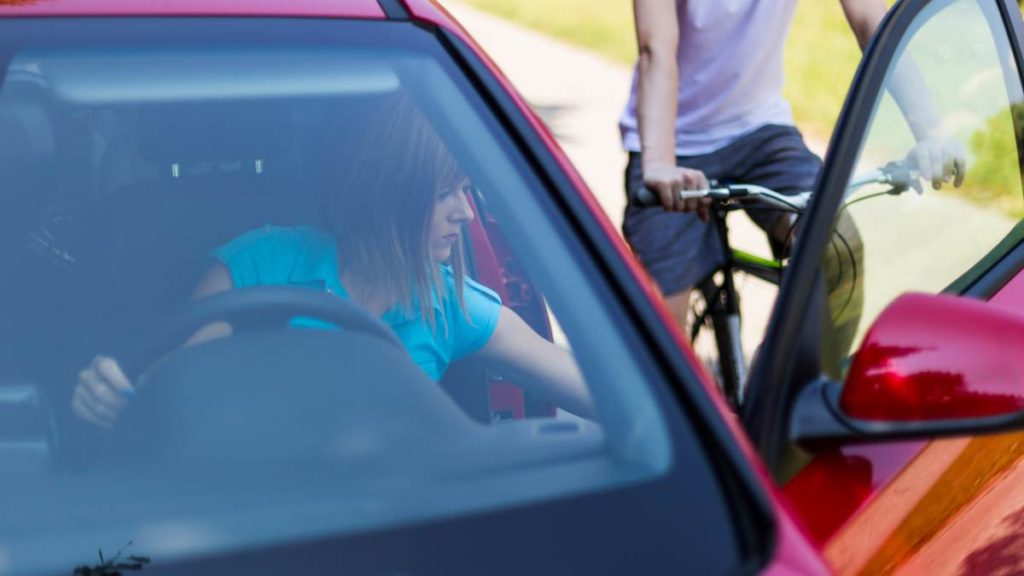 Woman in a car opening her door while a cyclist approaches.