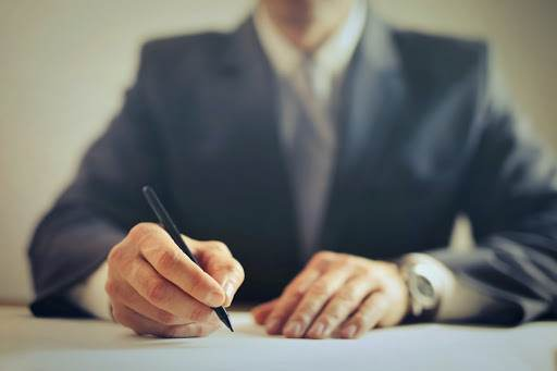 Man wearing a suit and signing a document.