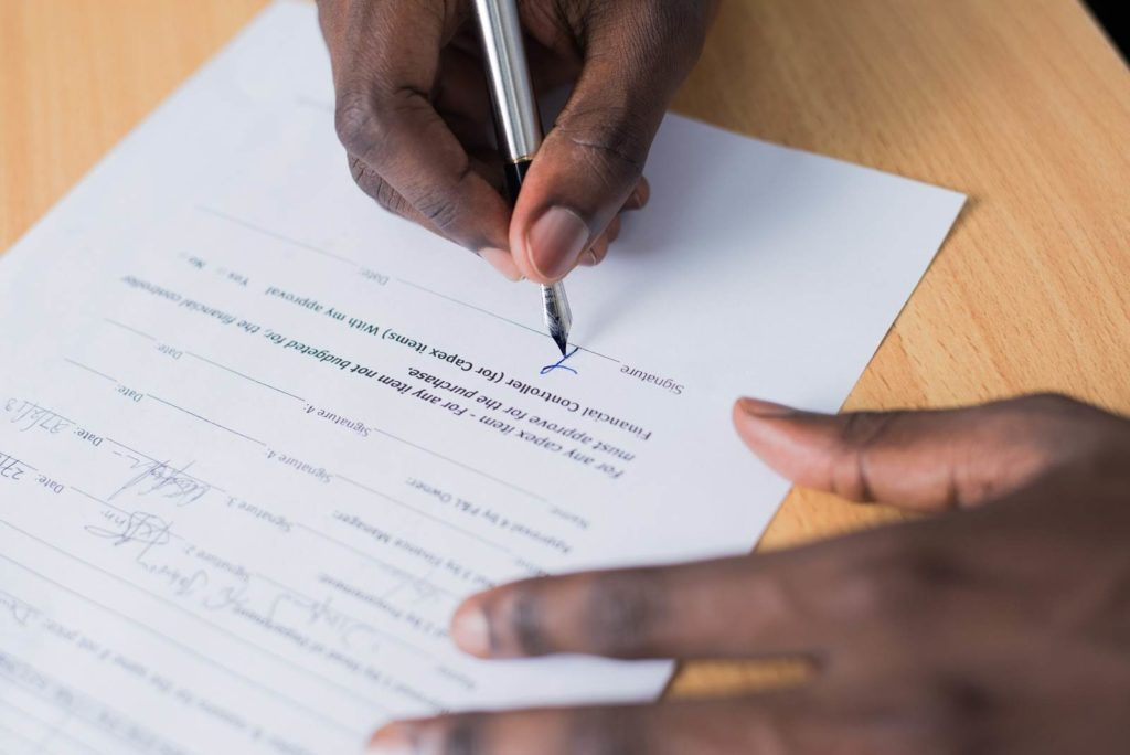 Close-up of a man's hands signing a contract.