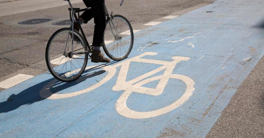 Cyclist riding in a blue painted bike lane.
