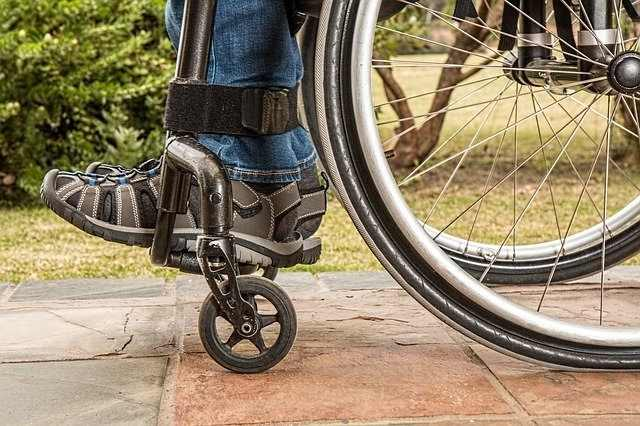 Close up of a person's legs and feet in a wheelchair.