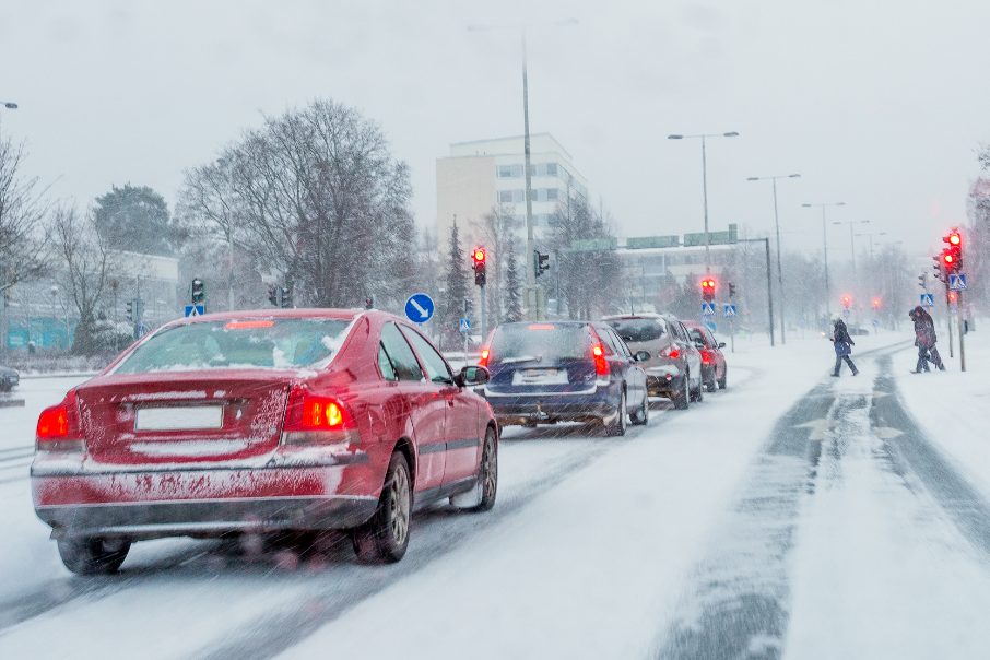 Cars lined up on a snowy road, waiting for pedestrians to cross.