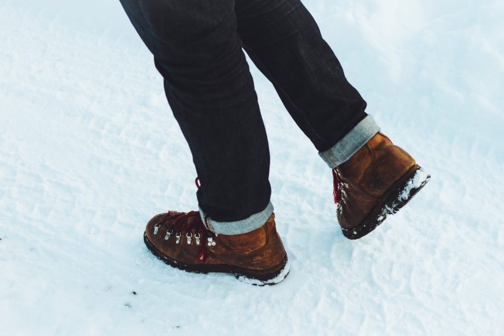 Legs seen from the knee down wearing jeans and brown boots, on a snowy ground.