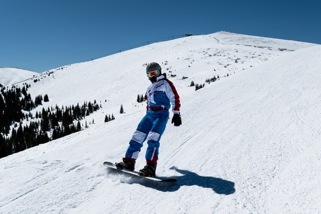A person in a snowsuit snowboarding down a hill.