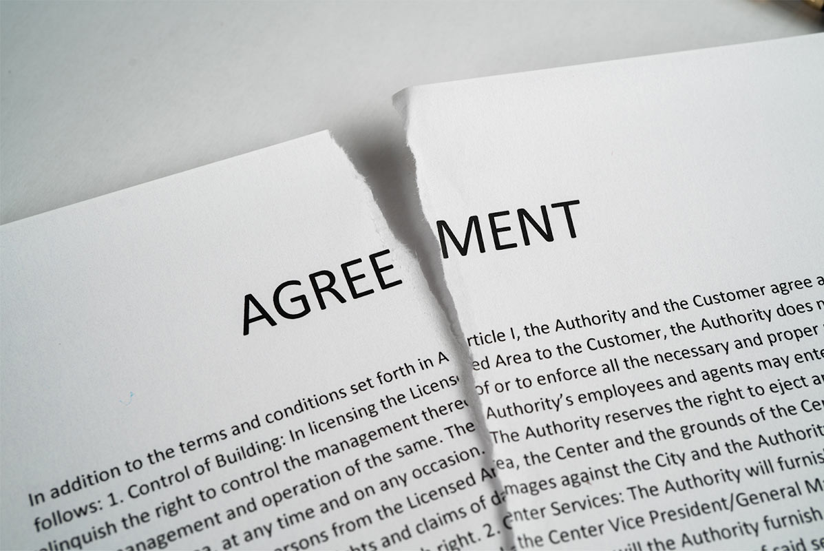 """A document with the heading """"Agreement"""" that has been torn down the middle."""