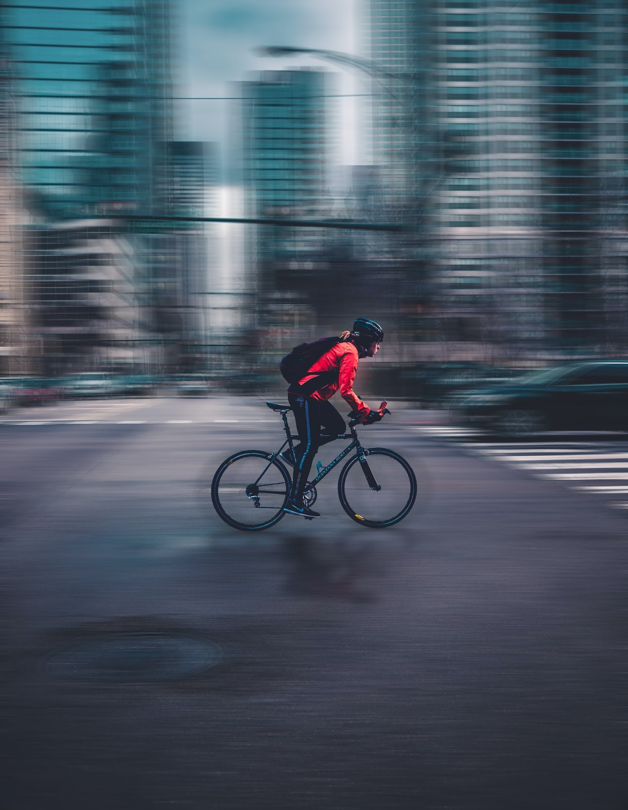 Cyclist wearing a helmet with a blurred city background.