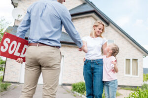 """Real estate agent holding a """"SOLD"""" sign and shaking hands with a woman and child in front of a house."""