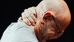 A man holding his neck in pain.