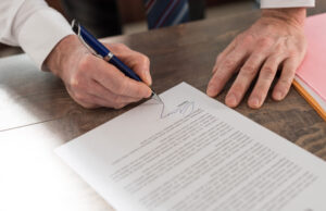 Close-up of hands signing a document.