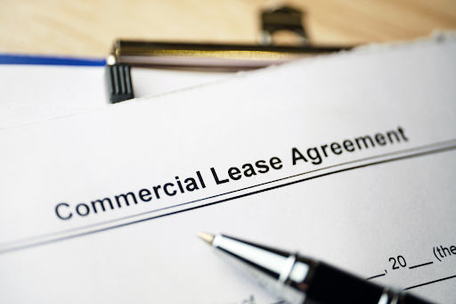 Commercial lease agreement document with a pen lying on it.