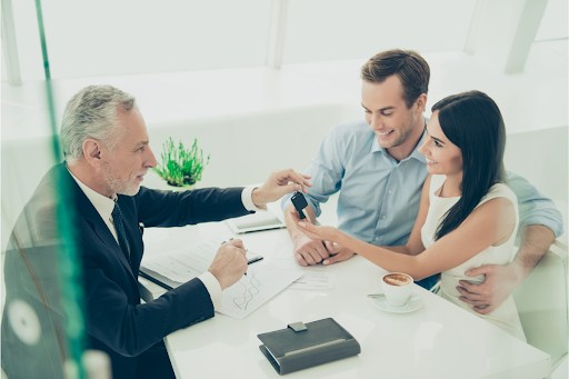 Real estate agent handing keys to a couple while filling out a contract.