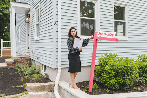 """Real estate agent standing beside a """"Sale Pending"""" sign in front of a house."""