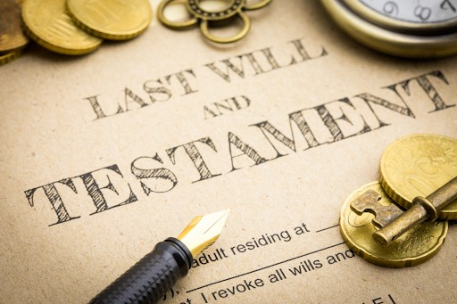 """Document reading """"Last Will & Testament"""" with a pen, key, and gold coins."""